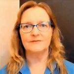 Silmälasipäiväinen nainen jolla on hartioille ulottuvat vaalenkuparin sävyiset hiukset ja sininen kauluspaita.